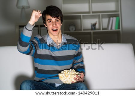 young man watching television with popcorn, raised his hand and cheering for their team