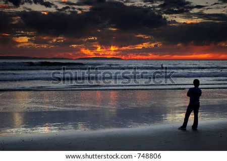 Young man watching the dramatic sunset on the beach.