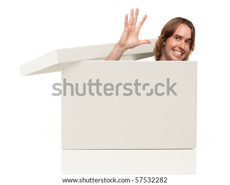 Young Man Waving His Hand and Popping His Head from a Blank White Box Isolated on a White Background - Box Ready for Your Own Message.