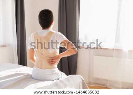 Young man wearing a back support belt. Lumbar brace, back support for back trauma or muscle back strain.