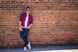 Young man wearing a check shirt and jeans against a brick wall