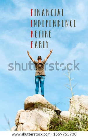 young man, wearing a green T-shirt and jeans, seen from behind, feeling free on the top of a rock, with his arms in the air and the word fire, acronym for financial independence retire early