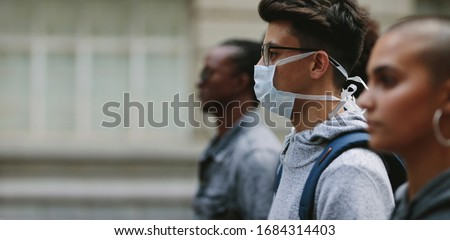 Young man wearing a mask participating in a protest with people around. Young people on a silent protest in the city.