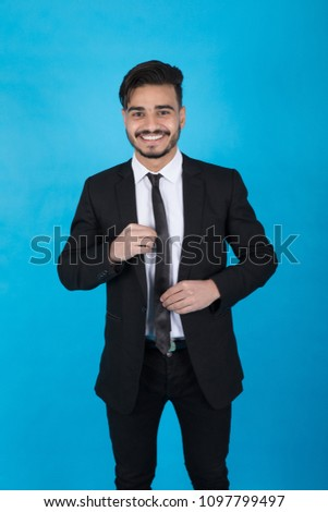 Young man wearing a suit adjusting the necktie he wears on a blue background. #1097799497