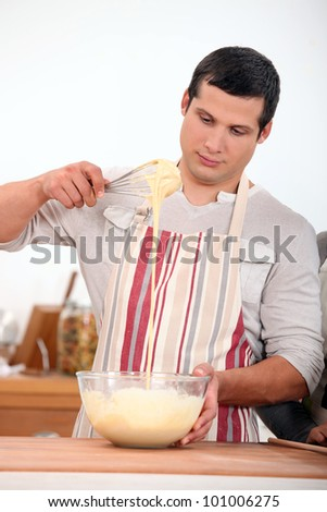young man wearing an apron and doing dough