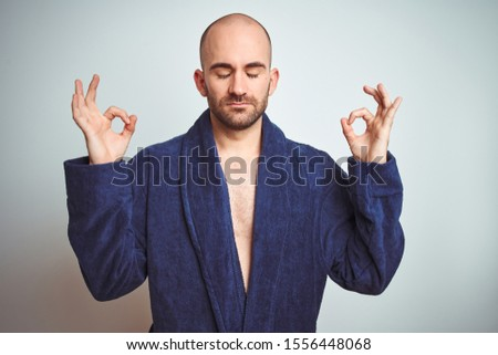 Young man wearing blue bathrobe, relaxed lifestyle over isolated background relax and smiling with eyes closed doing meditation gesture with fingers. Yoga concept.