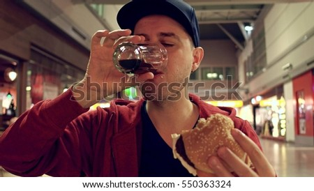 Young man wearing cap eats burger and drinks soft drink at the airport cafe Сток-фото ©