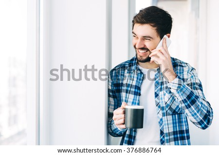 Young man wearing casual clothes talking on a mobile phone in the morning at a window with copy space,