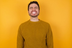 Young man wearing casual sweater and over isolated yellow background very happy and excited about new plans.