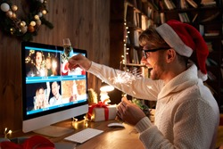 Young man wearing Christmas hat drinking champagne holding sparkler talking to friends on virtual zoom video call celebrate Happy New Year party in distance online conference chat on computer at home.