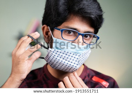 Young man wearing double or two face mask to protect from coronavirus or covid-19 outbreak - concept of safety, healthcare, medical and hygiene. Foto stock ©