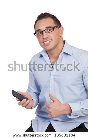 Young man wearing glasses holding a mobile phone giving a thumbs up of success or approval regarding news he has just received isolated on white