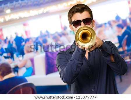 Young Man Wearing Goggles And Blowing Trumpet, Indoor