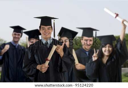 Young man wearing graduation cap and gown with classmates