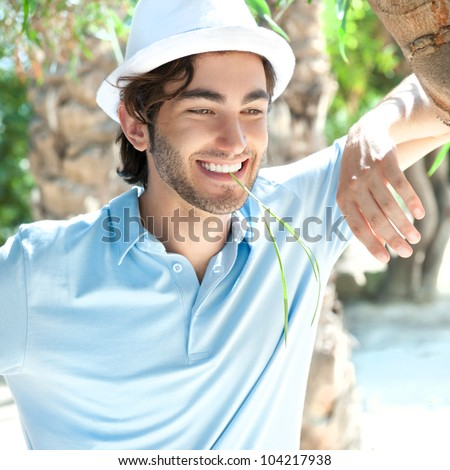Young man wearing hat and casual clothes in sunny day. Leaning on palm tree at summer park