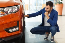 Young man wearing in stylish blue jacket sitting near orange jeep and examining size of wheel at car showroom. Handsome guy holding one arm on wheel and with another touching beard, focusing on tire.