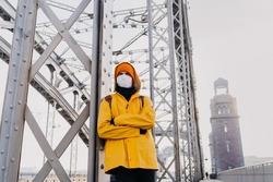 Young man wearing medical face mask, orange cap and yellow windbreaker beeingin upset mood, thinking about pandemic coronavirus, standing on the bridge in an empty city. Covid-19 virus concept.