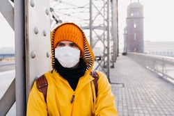 Young man wearing medical protective mask, orange cap and yellow windbreaker looking with concern, thinking about pandemic coronavirus, standing on the bridge in an empty city. Covid-19 virus concept.