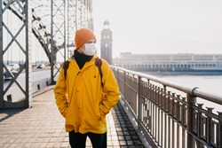 Young man wearing medical surgical mask, orange cap and yellow windbreaker looking with concern, thinking about pandemic coronavirus, standing on the bridge in an empty city. Covid-19 virus concept.