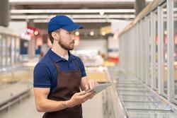 Young man wearing uniform working as merchandiser in modern supermarket using digital tablet, horizontal medium shot