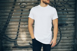 Young man wearing white blank t-shirt and blue jeans, standing on the street