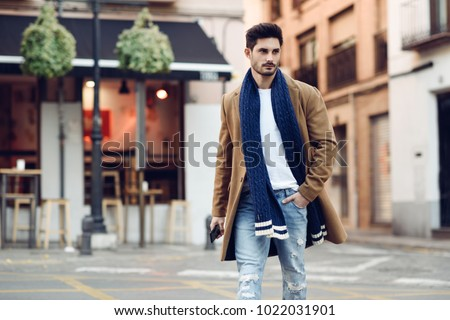 Young man wearing winter clothes with a smartphone in his hand, walking in the street. Young bearded guy with modern hairstyle in urban background.