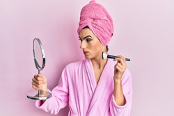 Young man wearing woman make up wearing pink robe applying blush skeptic and nervous, frowning upset because of problem. negative person.