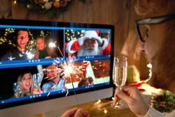 Young man wears Christmas hat drinking champagne holding sparkler talking to friends on virtual video call celebrate Happy New Year party in distance online chat at home, over shoulder screen view.