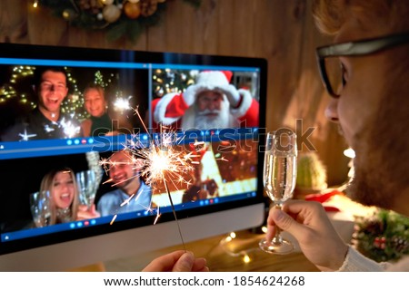 Photo of  Young man wears Christmas hat drinking champagne holding sparkler talking to friends on virtual video call celebrate Happy New Year party in distance online chat at home, over shoulder screen view.