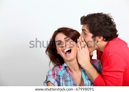 Young man whispering in his girlfriend's ear