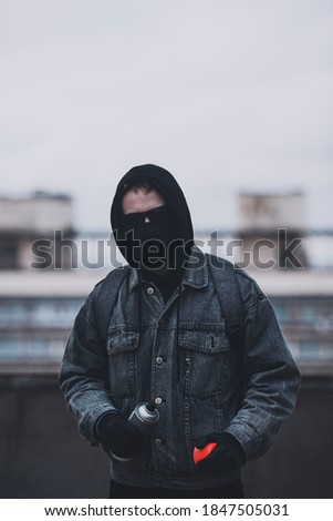 Young man who hides his face preparing to make graffiti. Urban view  stock photo