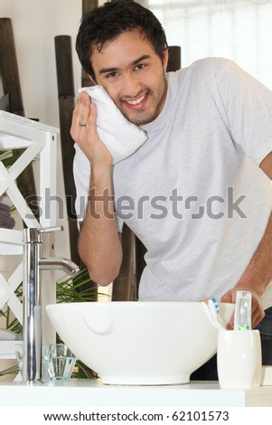 Young man wiping his face in the bathroom