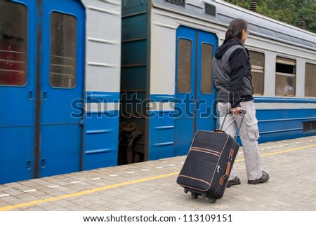 Young man with a baggage on the platform of a train station