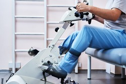 Young man with a broken spine is being rehabilitated in a specialized clinic overcoming pain. Rehabilitation therapy at the specialized bike. Kinesitherapy on motored. Mobilization and verticalization