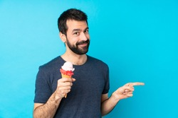 Young man with a cornet ice cream over isolated blue background pointing finger to the side