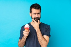 Young man with a cornet ice cream over isolated blue background thinking