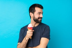 Young man with a cornet ice cream over isolated blue background with arms crossed and happy
