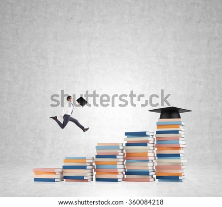Young man with a folder in hand running up stairs made of piles of books of different size, graduation hat on the highest, concrete background. Concept of higher education.