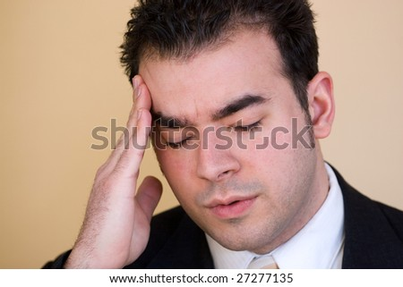 Young man with a headache. He might be experiencing intense stress over a time of economic downturn or other financial hardship.