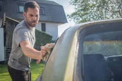 Young man with a hip beard cleaning a window of an old green vintage car on a home lawn. Cleaning muscle car windows at home with a cloth.