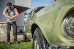 Young man with a hip beard cleaning a wringing a cloth while cleaning an old green vintage car on a home lawn. Cleaning muscle car at home with a cloth.