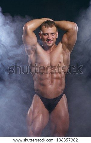 Young man with a perfect muscle body on dark with smoke