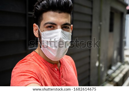 Young man with a protective mask making a selfie on the street