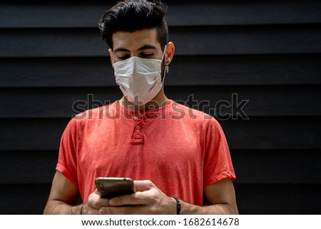 Young man with a protective mask wearing his mobile phone in the middle of the street in front of a blue wooden wall