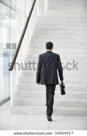 Young man with a suitcase climbing stairs - stock photo