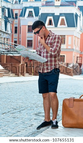 Young man with a suitcase in a thoughtful look at the map on city street. - stock photo
