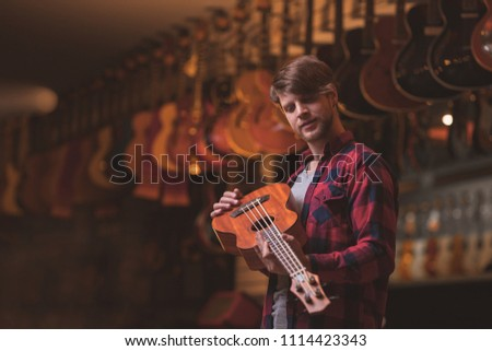 Young man with a ukulele in a music store