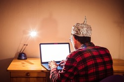 Young man with aluminum cap is sitting in the dark basement in front of a laptop. Conspiracy theory concept