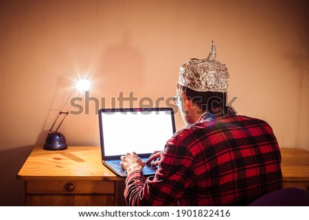 Young man with aluminum cap is sitting in the dark basement in front of a laptop. Conspiracy theory concept Foto stock ©