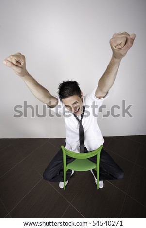 Young man with arms in the air, sitting on a chair cheering